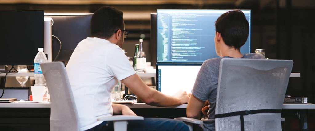 Dos ingenieros de software decididos a programar una línea de código inigualable, se encuentran sentados frente a sus computadoras.