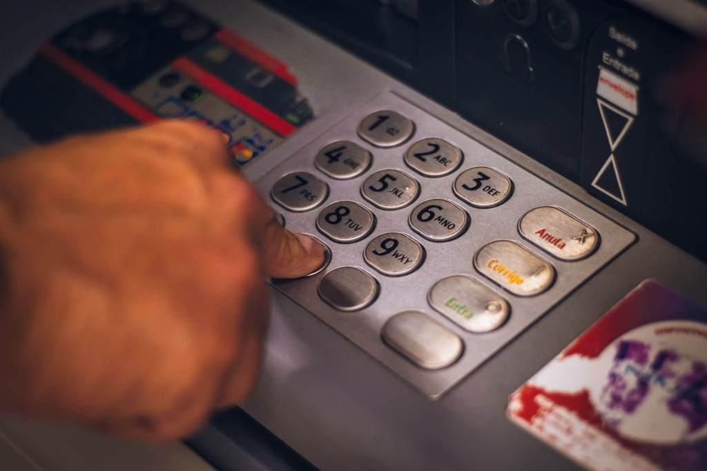 Una mano teclea dígitos en un cajero automático: comisiones bancarias se cobran en exceso.