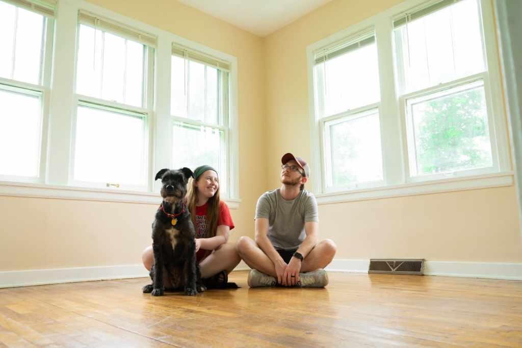 Pareja joven sentados en el piso de una casa nueva junto con su perro disfrutan de metas financieras sólidas con el método Nu