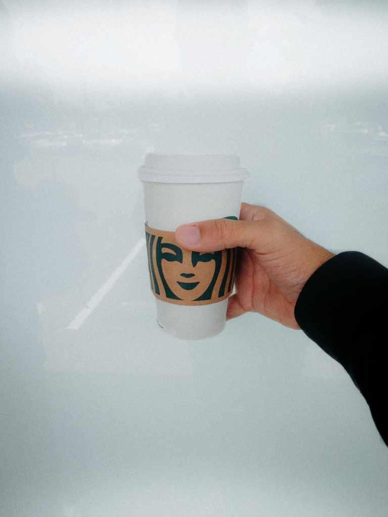 Mano sostiene un café en vaso desechable frente a una ventana ejemplificando uno de los hábitos que no te dejan ahorrar dinero