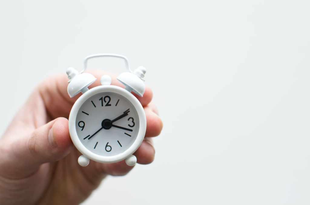 Mano sostiene pequeño reloj despertados de color blanco como recordatorio de herramienta para manejar un calendario financiero