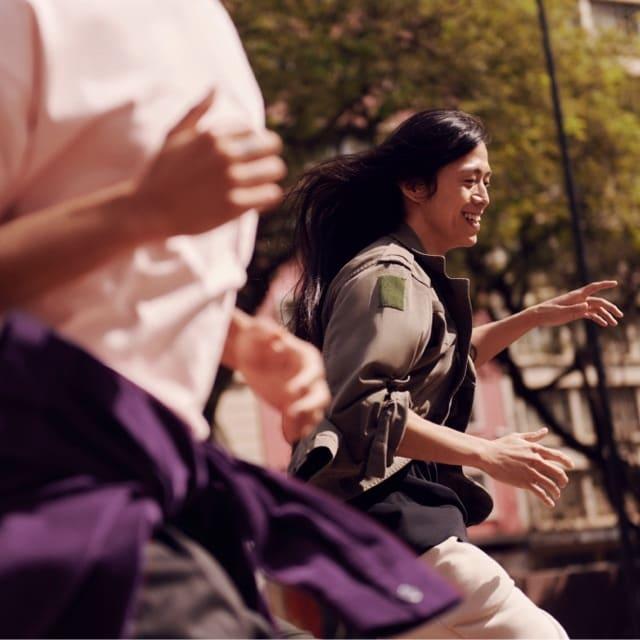 Mujer con chamarra verde militar corre entre un grupo de gente: Nu aparece en el listado CNBC Disruptor 50