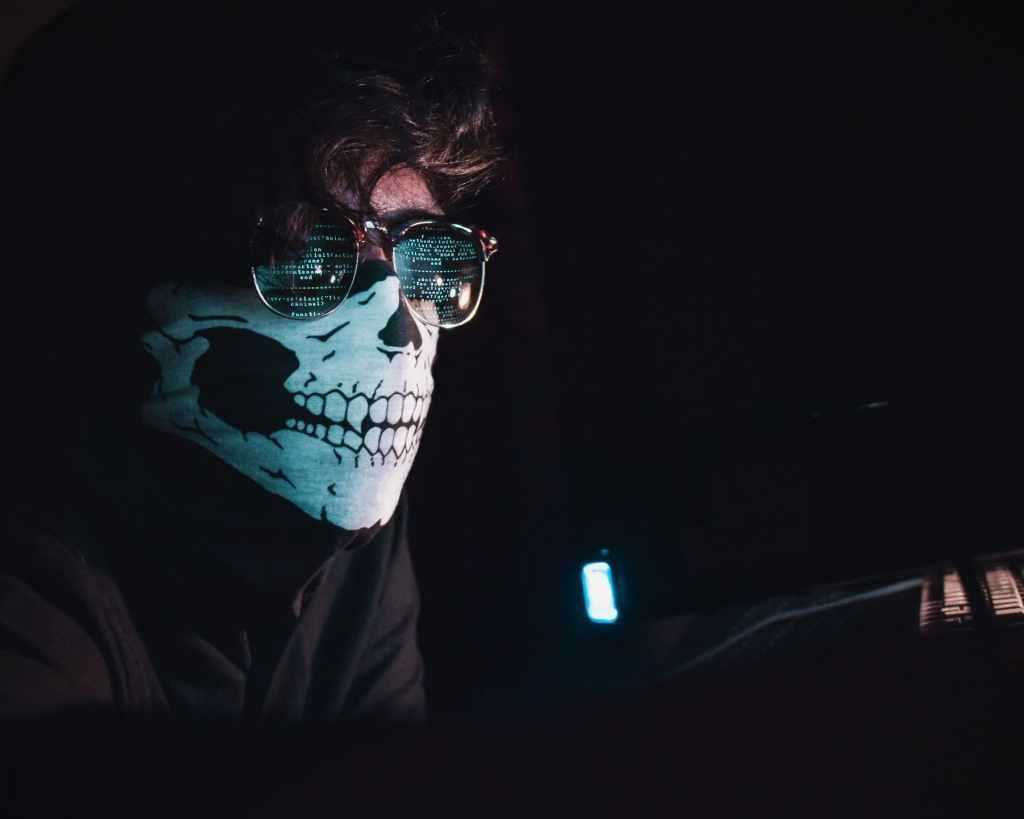 Hacker con pañoleta en la obscuridad realiza fraude de transacciones