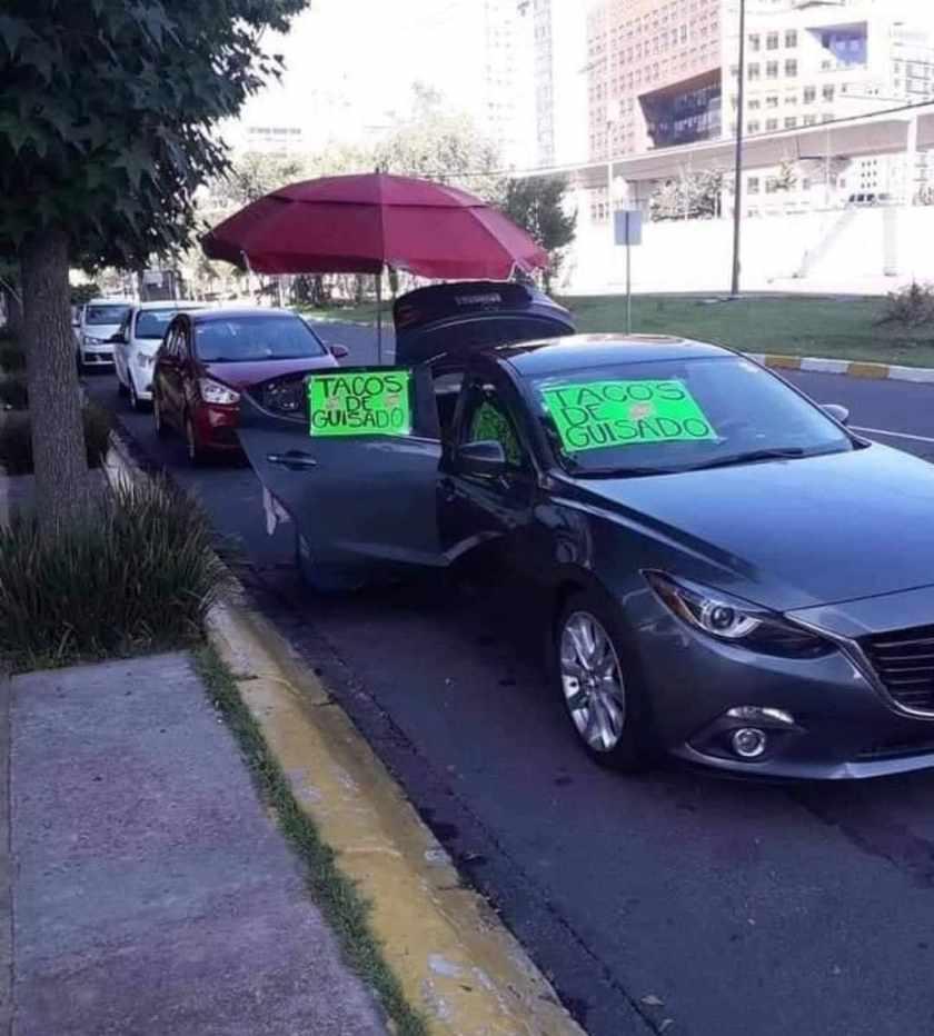 Carro azul estacionado con letreros de venta de tacos para cambiar mi futuro