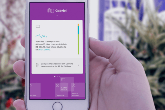Imagem de uma mão segurando um celular com a tela do app do Nubank aberta e os ícones de atalho reordenados