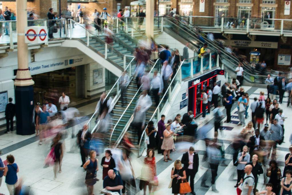 Imagem de um espaço comercial com escadas rolantes e pessoas se mexendo muito rápido