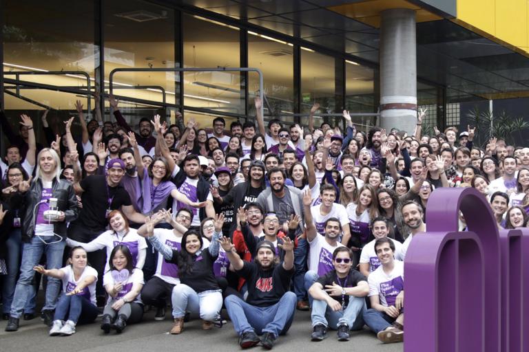 Foto na frente do escritório do Nubank, com a placa da empresa e um grupo de mais de 200 pessoas erguendo as mãos