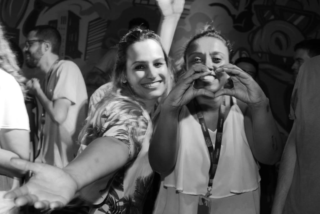 Duas jovens em uma festa, sorrindo para a câmera. Uma delas está fazendo um coração com as mãos. A foto é em preto e branco