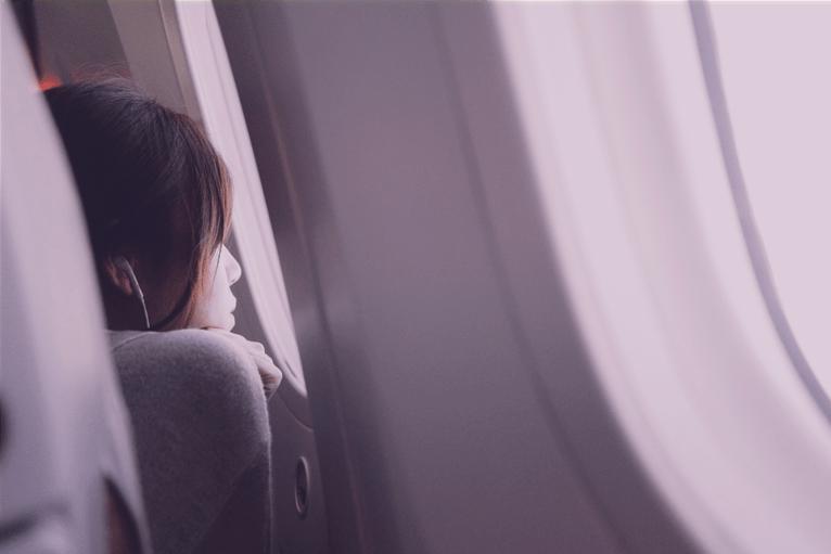Jovem está com a testa quase encostada na janela do avião, olhando para fora