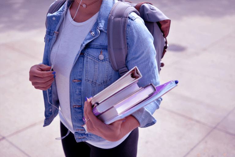 foto mostra tronco de uma jovem de camiseta branca, jaqueta jeans e mochila, carregando livros