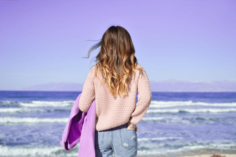 Jovem de cabelos compridos e blusa branca, de costas, segurando um cobertor roxo e olhando para o mar em um dia ensolarado