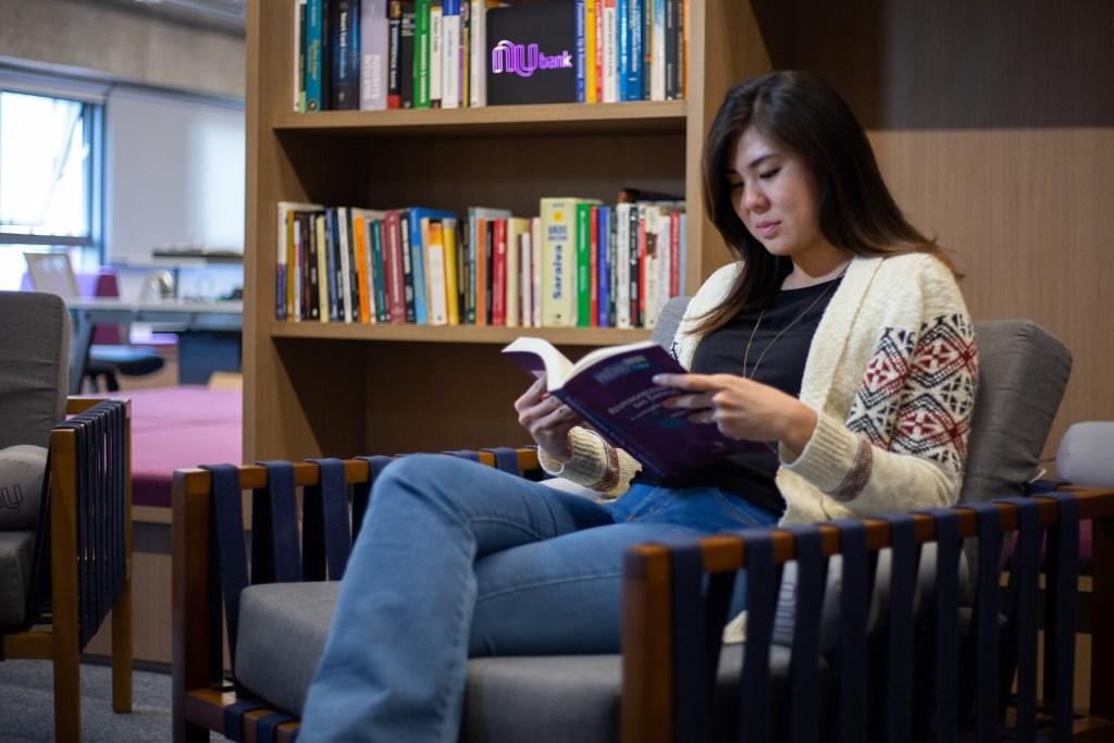 Jovem sentada em uma poltrona na biblioteca do Nubank. Atrás dela, uma parede de livros.