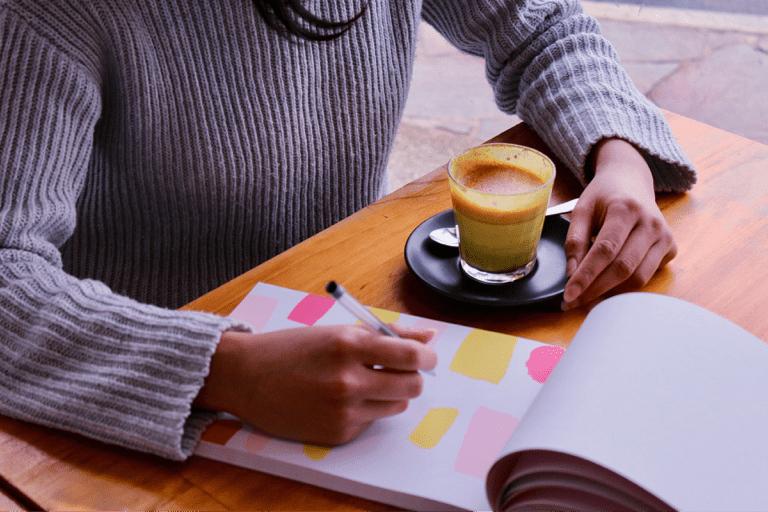 Pessoa sentada em uma mesa, comum café e um bloco de anotações