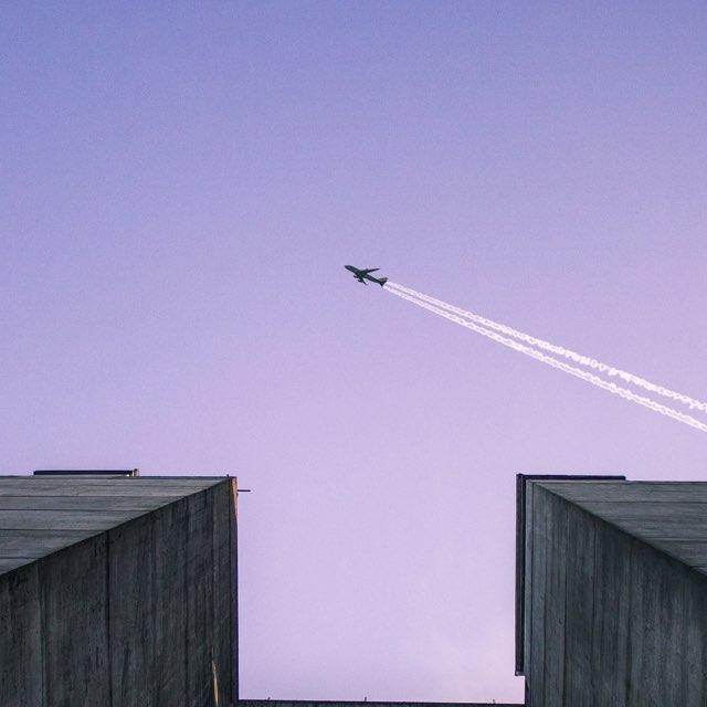 Foto de um avião passando em cima de dois prédios, deixando um rastro de fumaça no céu arroxeado