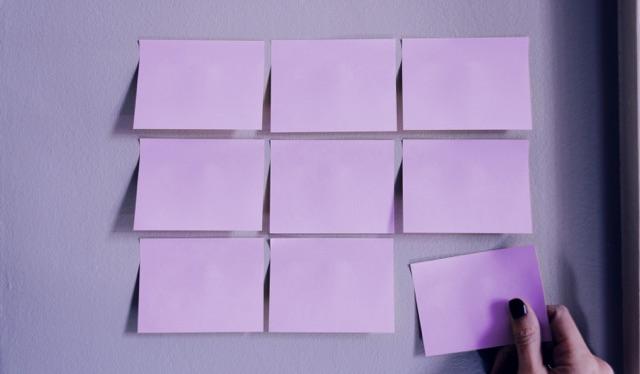 Nove post its roxos colados na parede e uma mão com unhas pintadas de preto removendo um deles