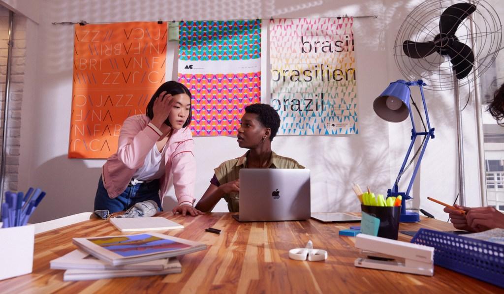 Como economizar dinheiro: duas jovens conversando. Uma delas está sentada na mesa em frente ao computador. A outra está de pé, ao seu lado