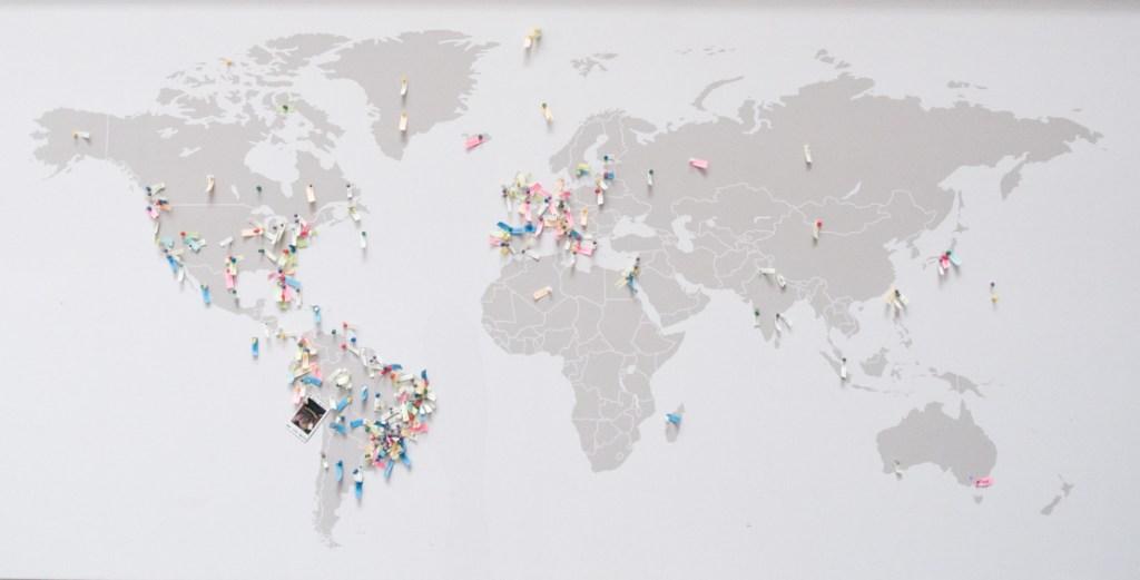 Mapa Mundi cinza com pins em diversos países e cidades.