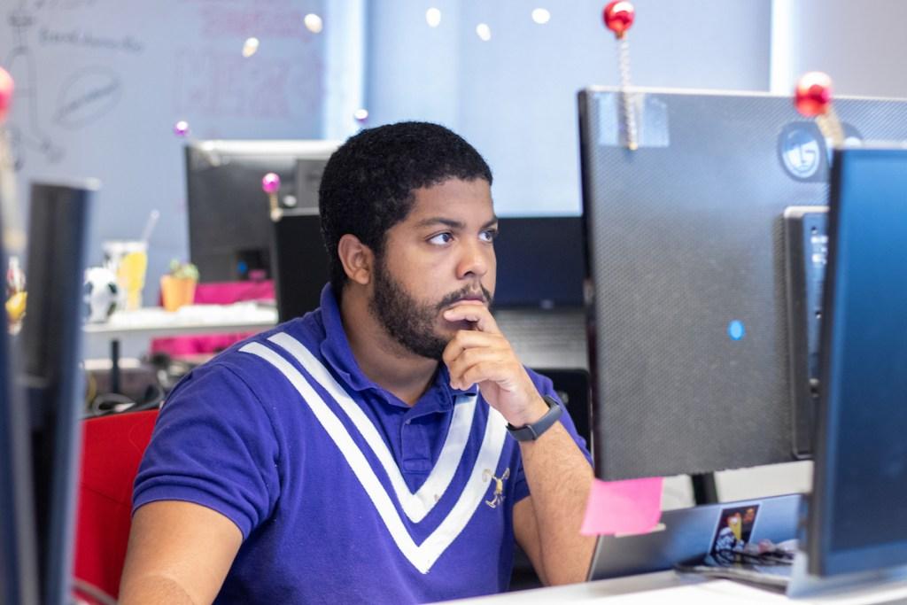 Um homem com a mão no queixo olha para a tela do computador.