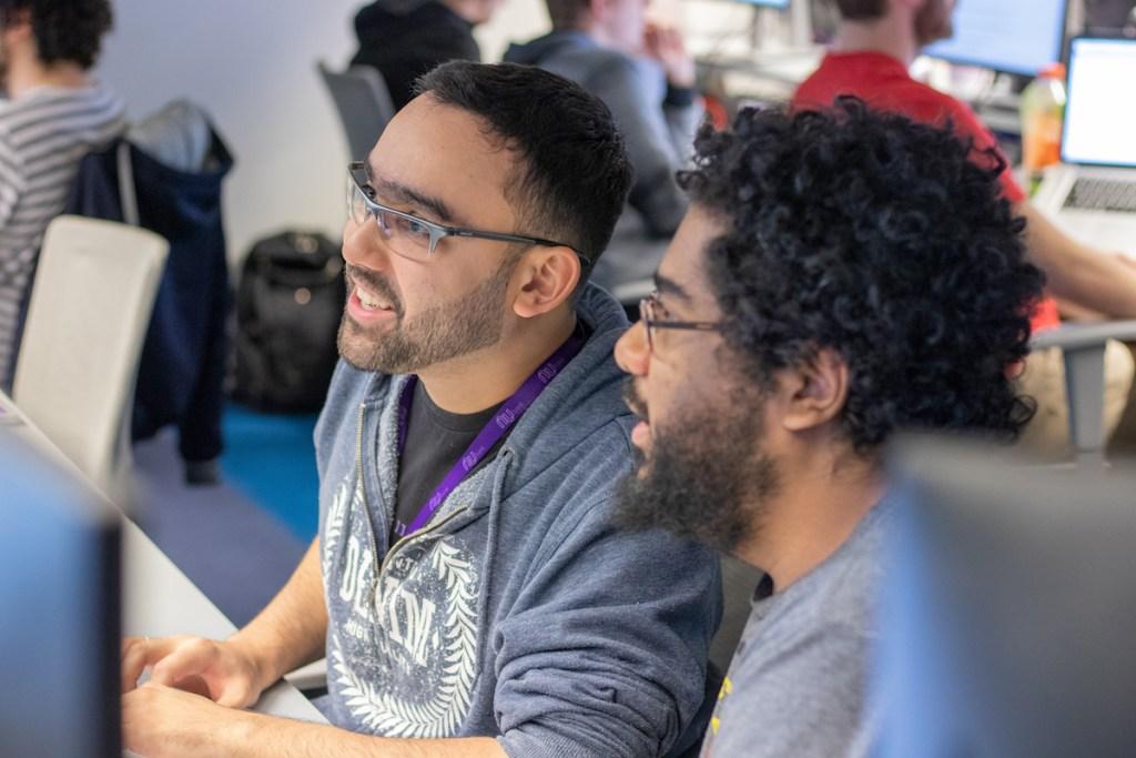 Dois homens olhando para uma tela de computador e trabalhando juntos