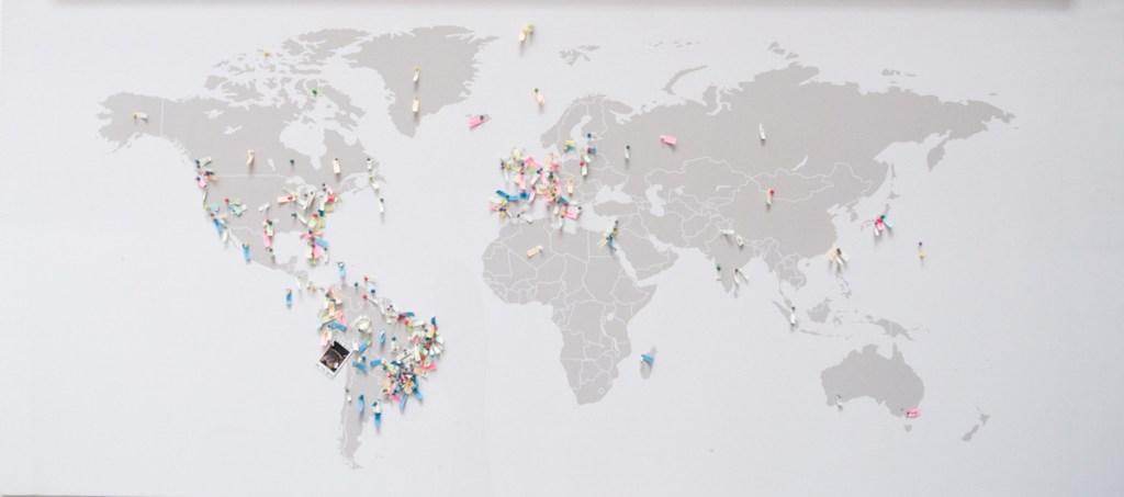 Mapa mundi com diversos alfinetes espalhados indicando lugares do mundo