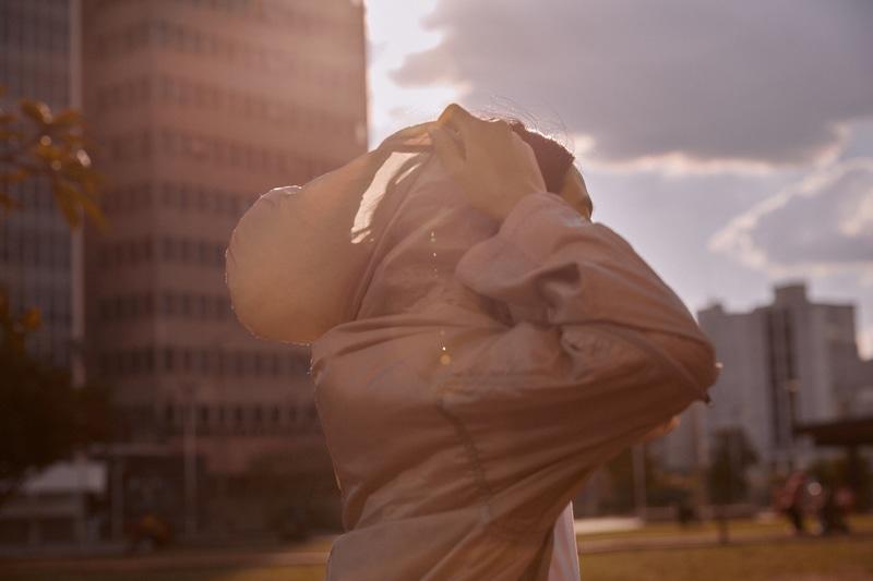 Mulher colocando o capuz ao ar livre
