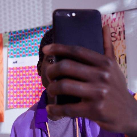Atualização app Nubank: um homem segura o celular na frente do rosto e olha para a tela.