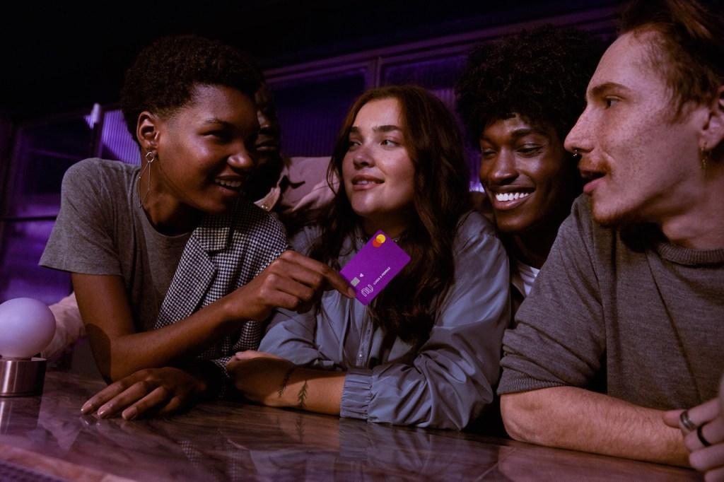 Foto de quatro pessoas no balcão de um restaurante. Uma das pessoas, uma mulher, está segurando o cartão Nubank.