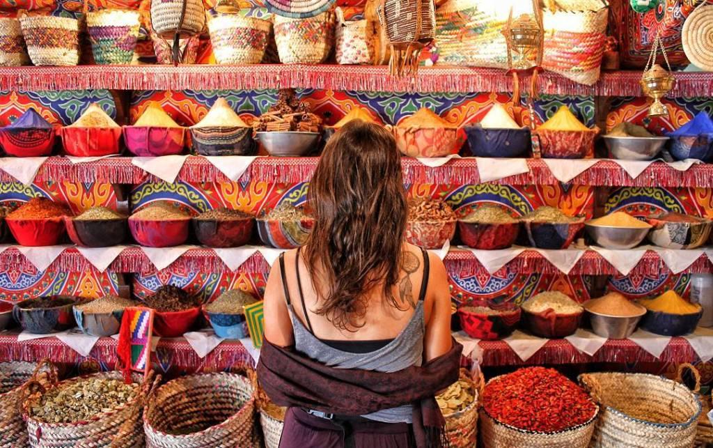 Mochilão: mulher de costas em frente a vários temperos coloridos em um mercado