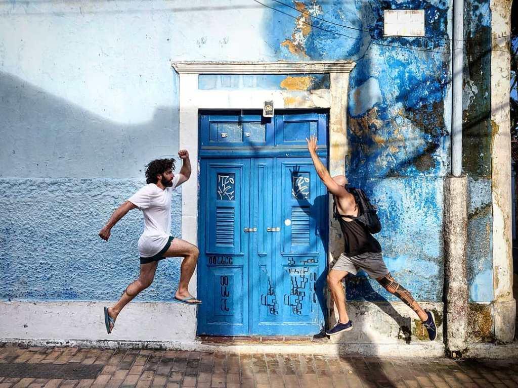 Mochilão: dois homens em frente a parece e porta azul correndo um em direção ao outro