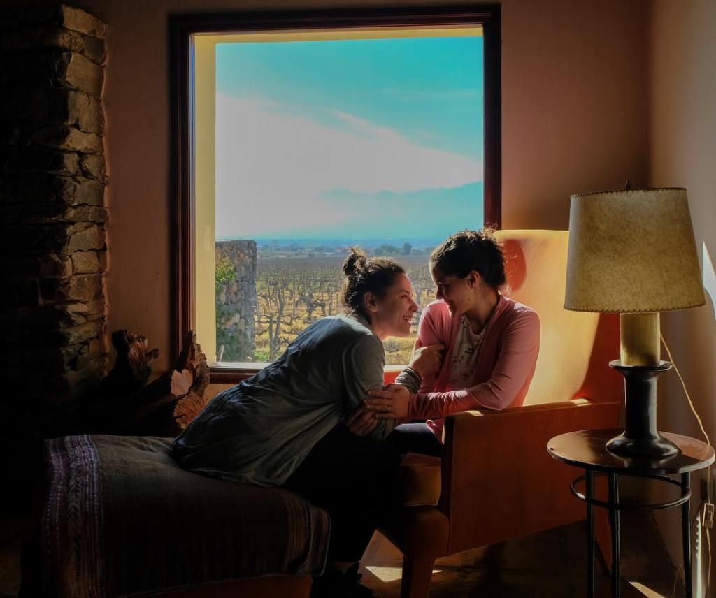 Mochilão: Duas mulheres sentadas em quarto de hotel sorrindo