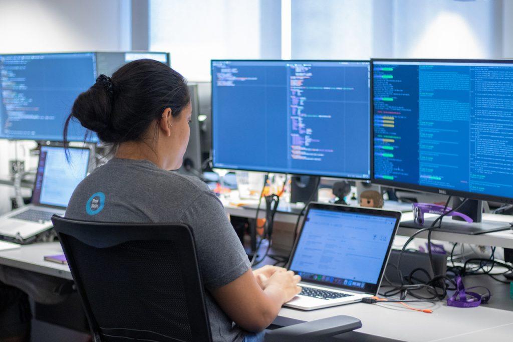 Uma mulher codando com um notebook e dois monitores