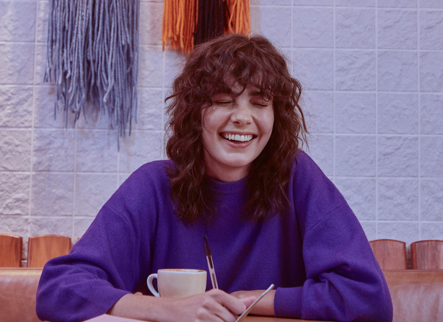 Freela: mulher sorrindo vestida de moletom roxo e segurando uma caneta e uma caneca