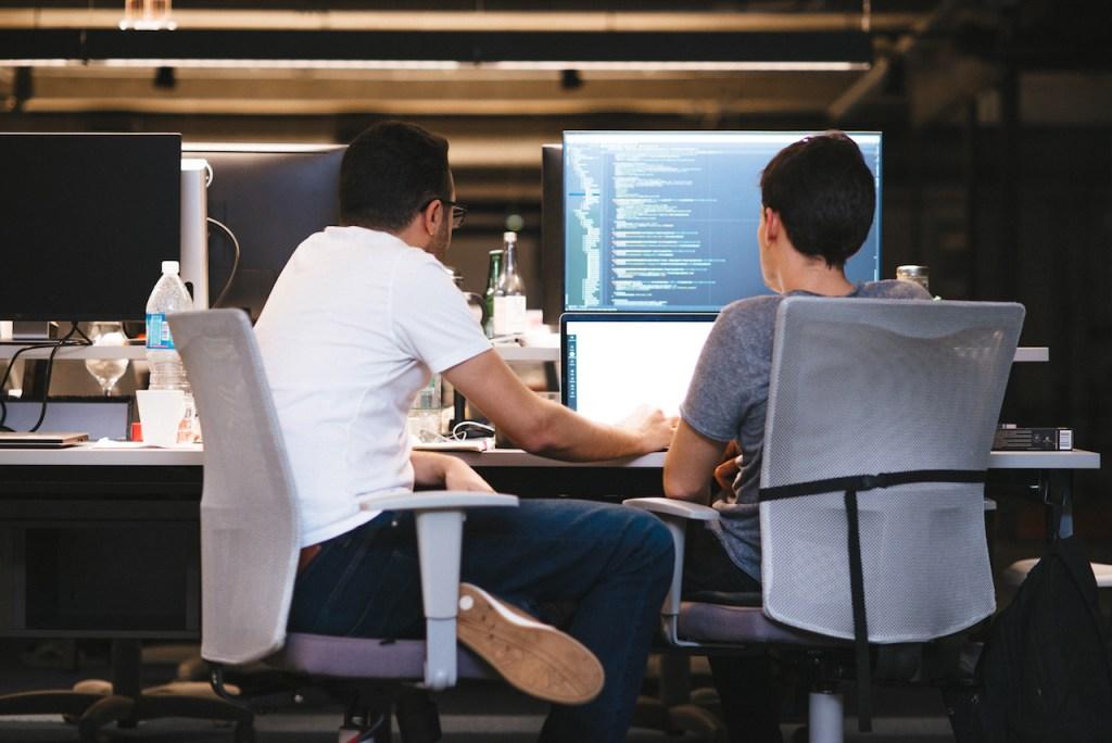 dois homens sentados olhando para um computador. Na segunda tela, um programa de código de programação.