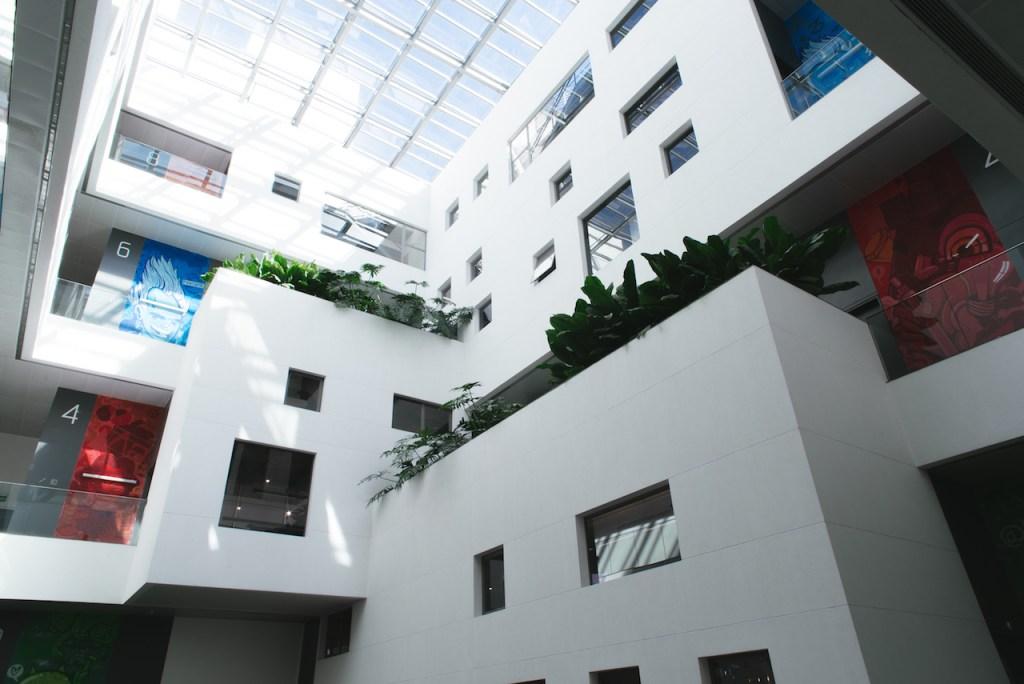 Foto interna da sede do Nubank, em São Paulo: um vão interno com teto de vidro.