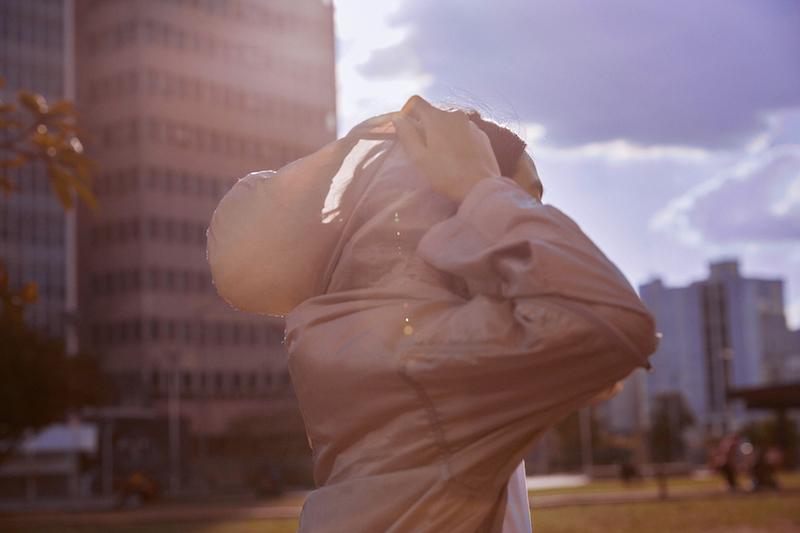 Metodologia ágil: mulher no parque colocando o capuz de um casaco