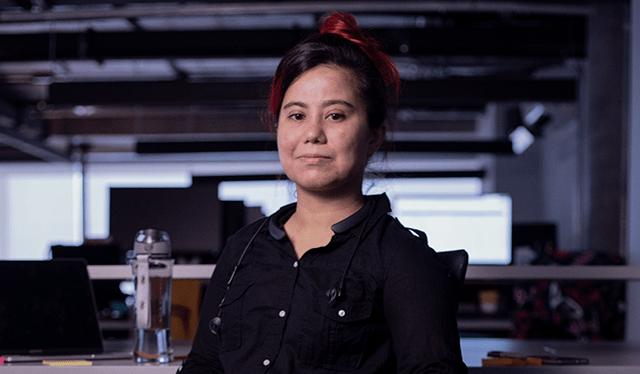 Mulheres no Nubank: foto de Ceci Fernandes no escritório do Nubank. Ela usa roupas pretas e tem o cabelo, vermelho, preso.