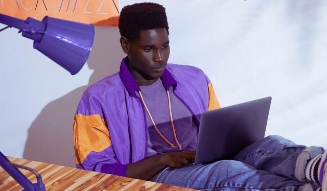 Homem vestindo jaqueta roxa sentado com os pés sobre a mesa e trabalhando em um notebook