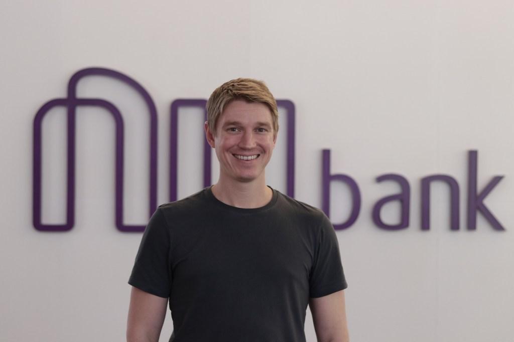 Fotografia de Edward Wible em frente ao logo do Nubank