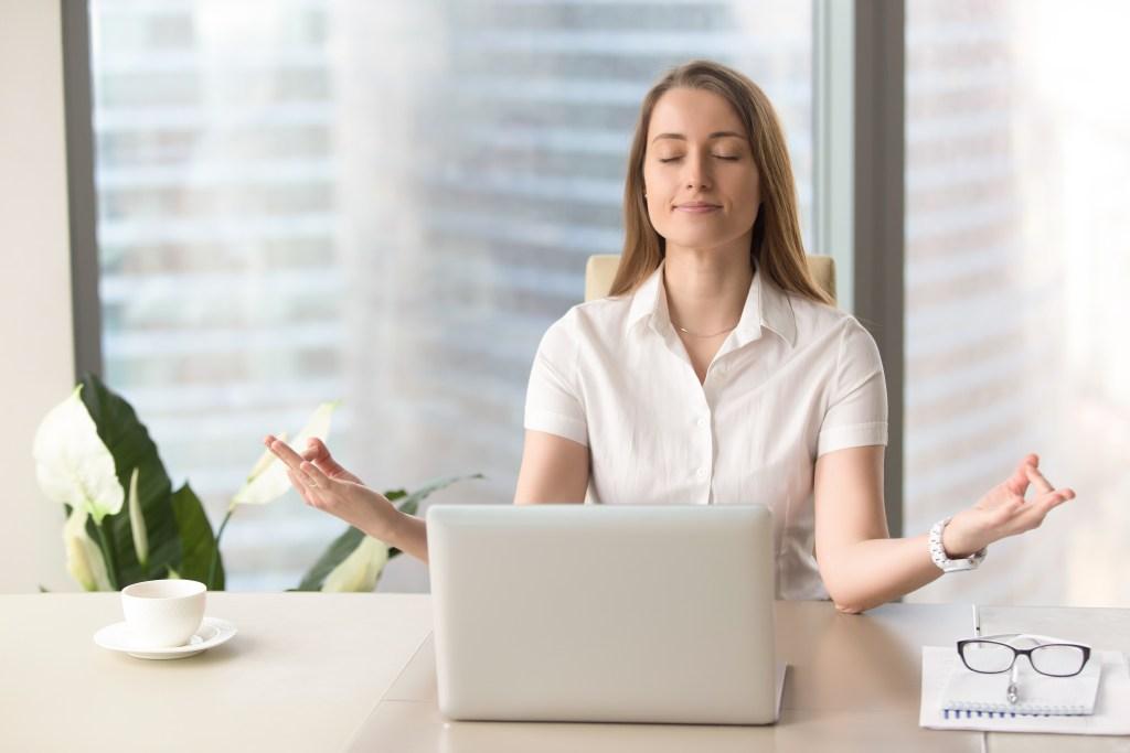 Mulher meditando em seu escritório e em frente ao computador