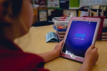 Child using iPad showing objective ed logo