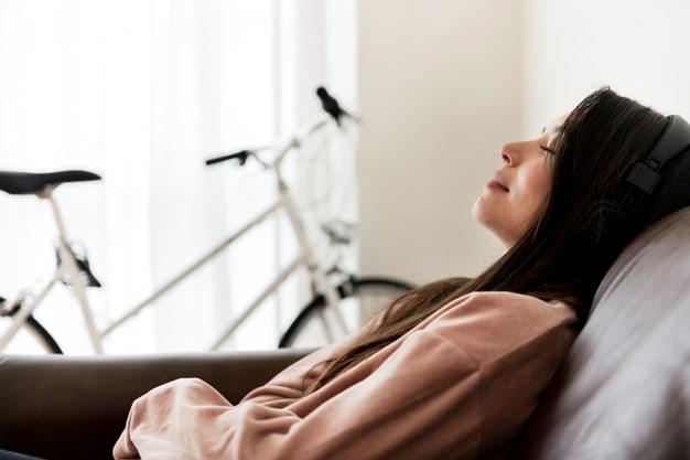 jovem mulher caucasiana a descansar na sofá da sala de estar com o ar condicionado ligado