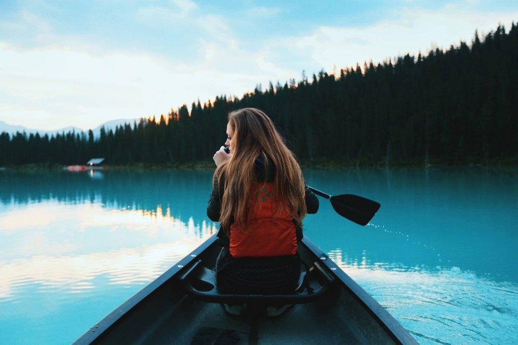 Mulher jovem a fazer canoagem durante as férias