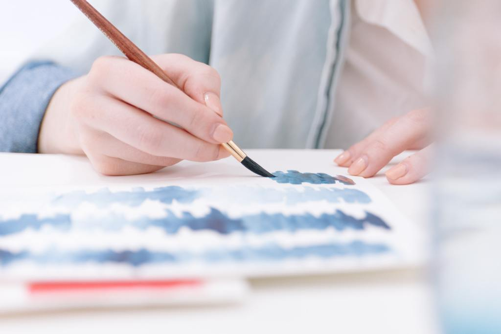 Mulher jovem grávida a pintar uma tela para a decoração do quarto do seu bebé