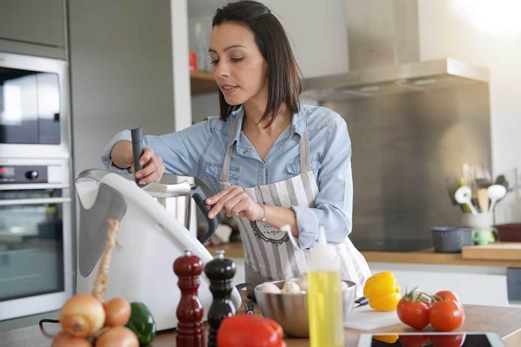 Mulher a preparar o jantar com robot de cozinha