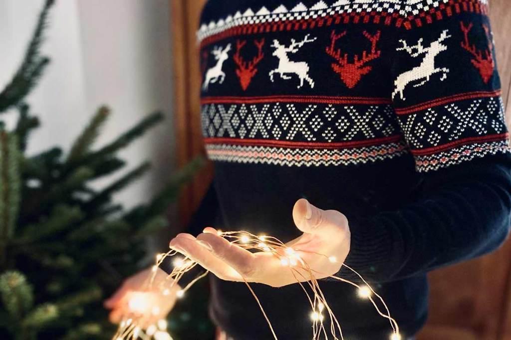Homem com camisola de natal a segurar nas luzes de natal