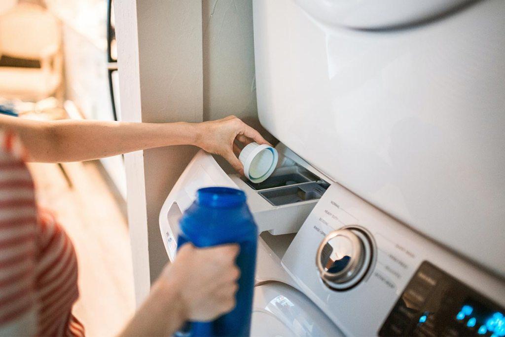 Mulher a pôr a máquina de lavar a roupa