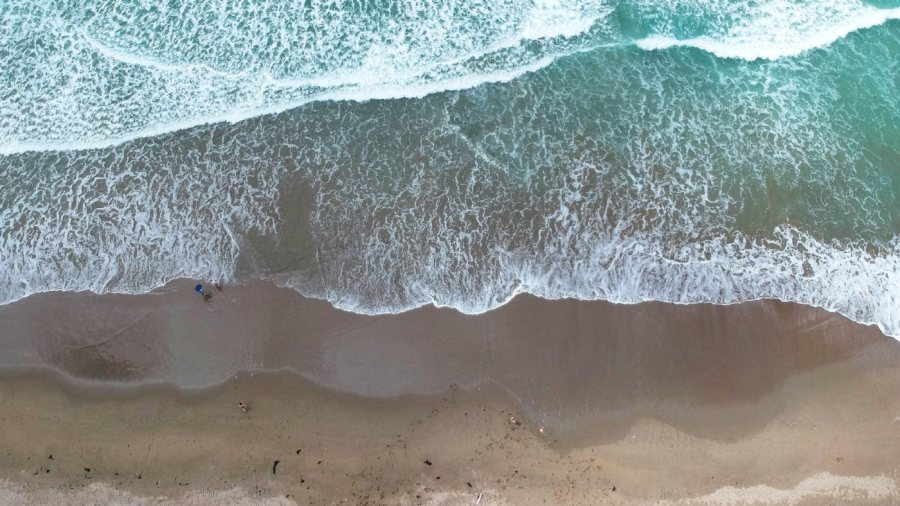 An aerial photo looking down at beach and surf, taken by a drone.
