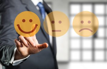 Geschäftsmann wählt lächelnden Smiley vor Bürohintergrund