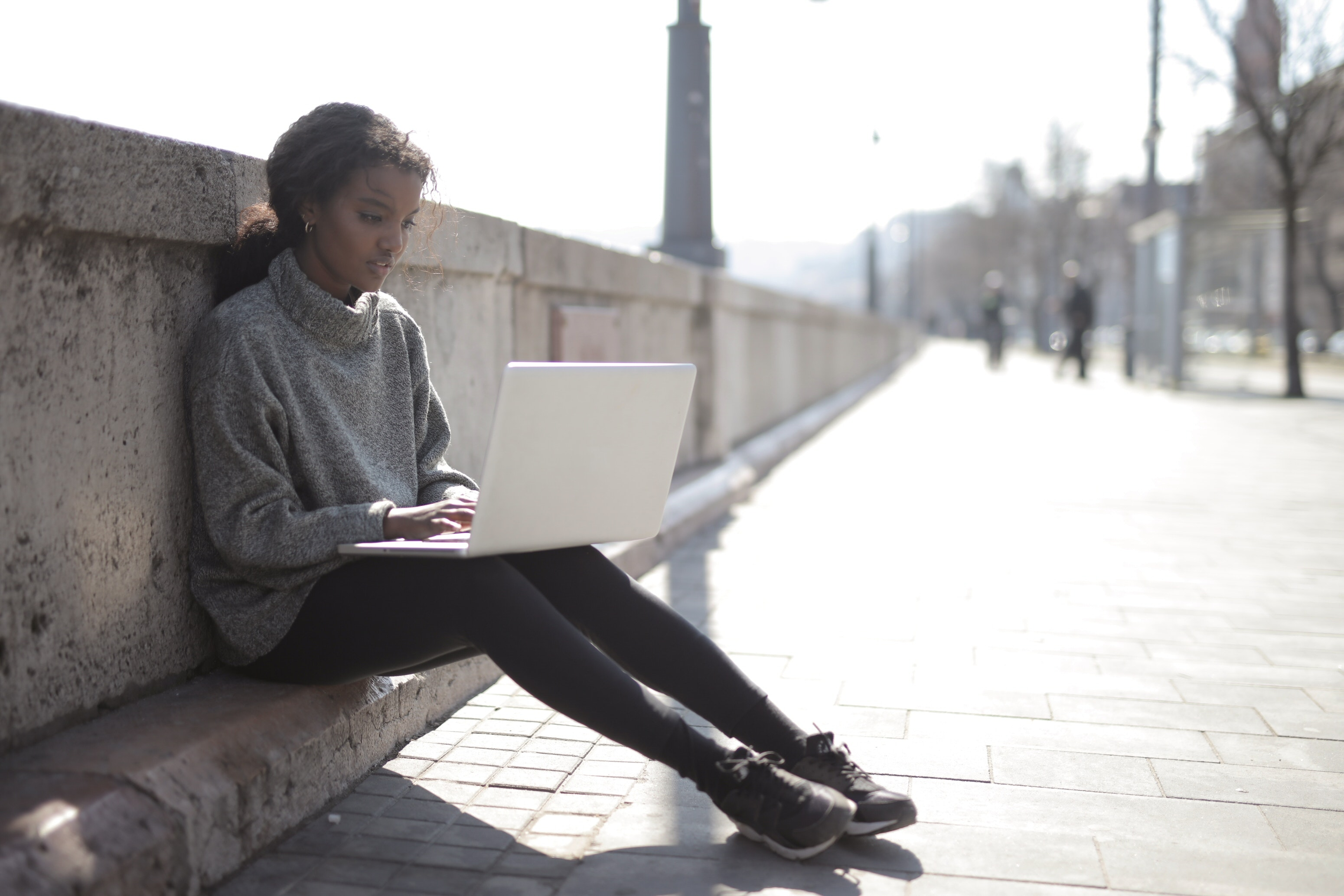 A woman in a grey sweater using her laptop outside, sitting against a bridge wall.