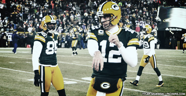 Aaron Rodgers warms up his arm as Greg Jennings looks on